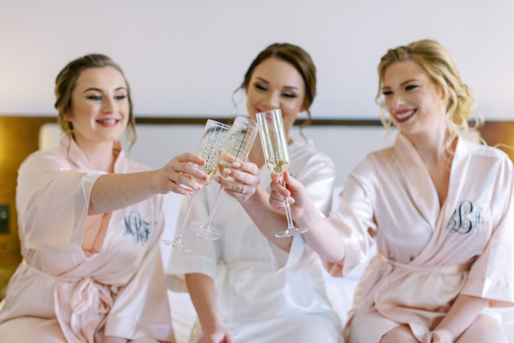 bride and bridesmaids popping champaign. Bride planned ahead so she could enjoy her wedding morning